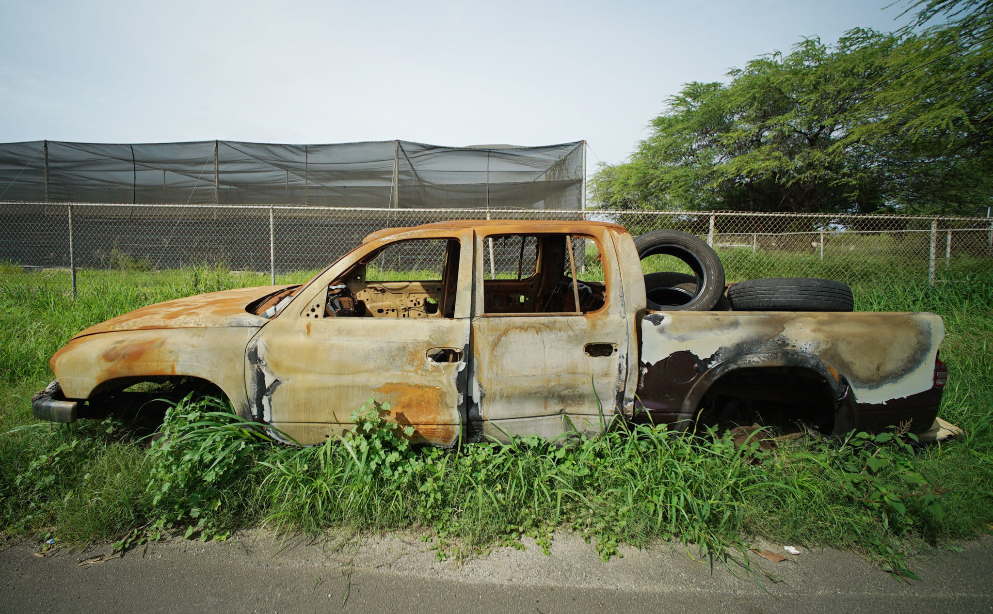 <p>Many abandoned vehicles like this one along Kaukamana Road in Waianae are burned out and gutted.</p>