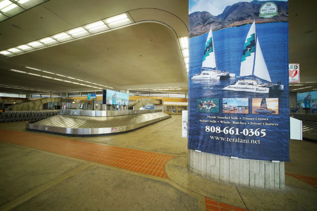 OGG Maui Airport baggage claim large advertisements.