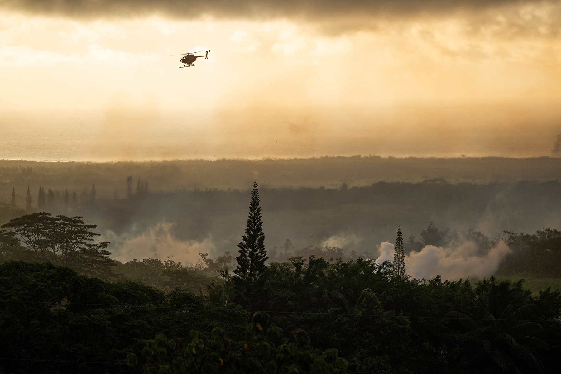 <p>A Civil Defense helicopter surveys an eruption from the newest volcanic fissure in the Lower Puna area early Sunday morning.</p>