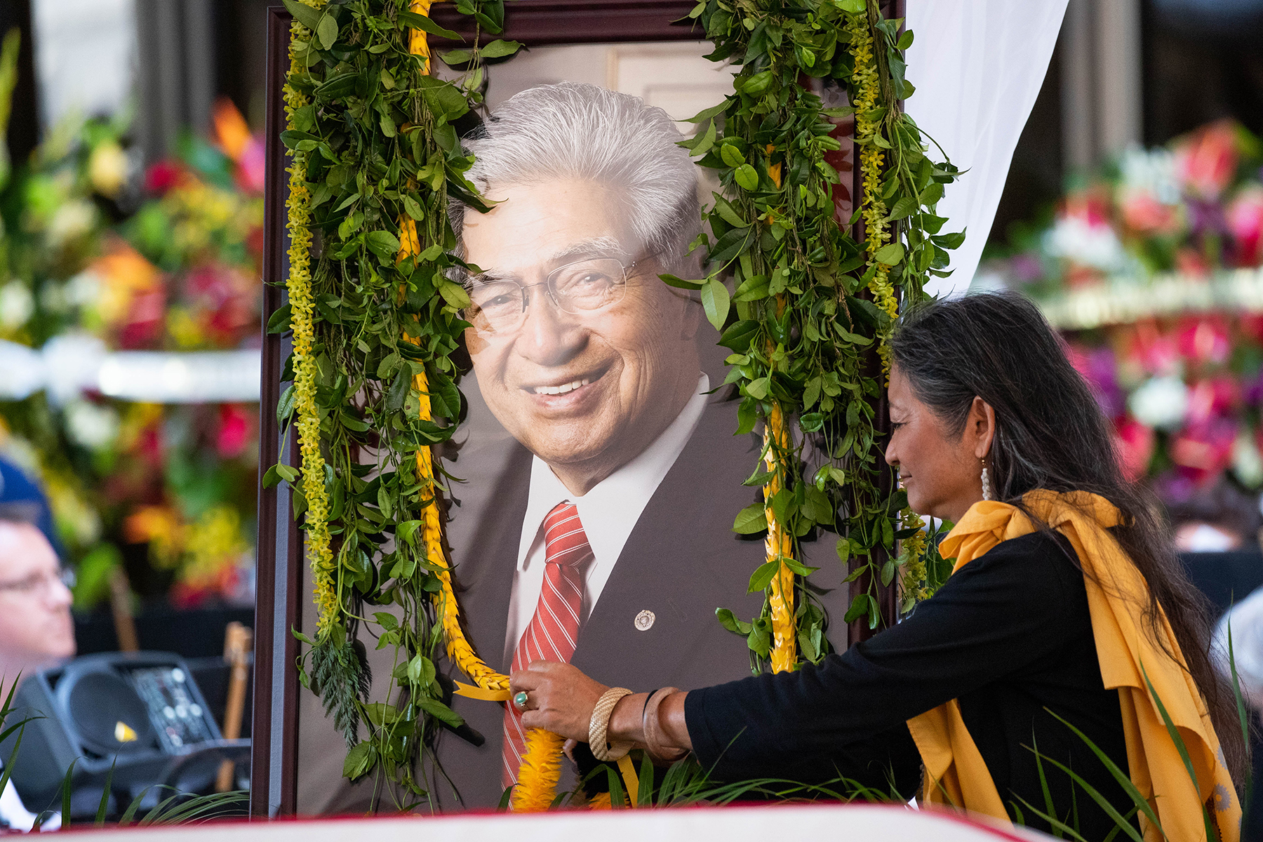 <p>Anna Akaka, one of Sen. Daniel Akaka's daughters-in-law, rests lei on a mural behind the casket. <span class=