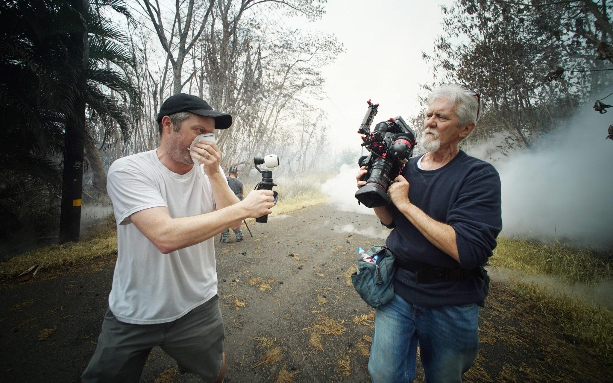 <p>Tim Coakley films Leilani Estates resident and volcano filmaker Mick Kalber along Kahukai Street.</p>