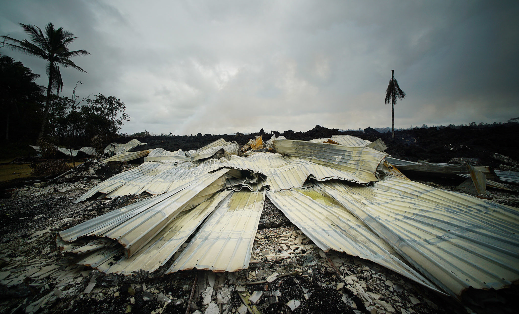 <p><strong>GROUND ZERO:</strong> Aluminum roofing material lay on the foundation of a home that was engulfed by lava in the Leilani Estates neighborhood. / Cory Lum</p>