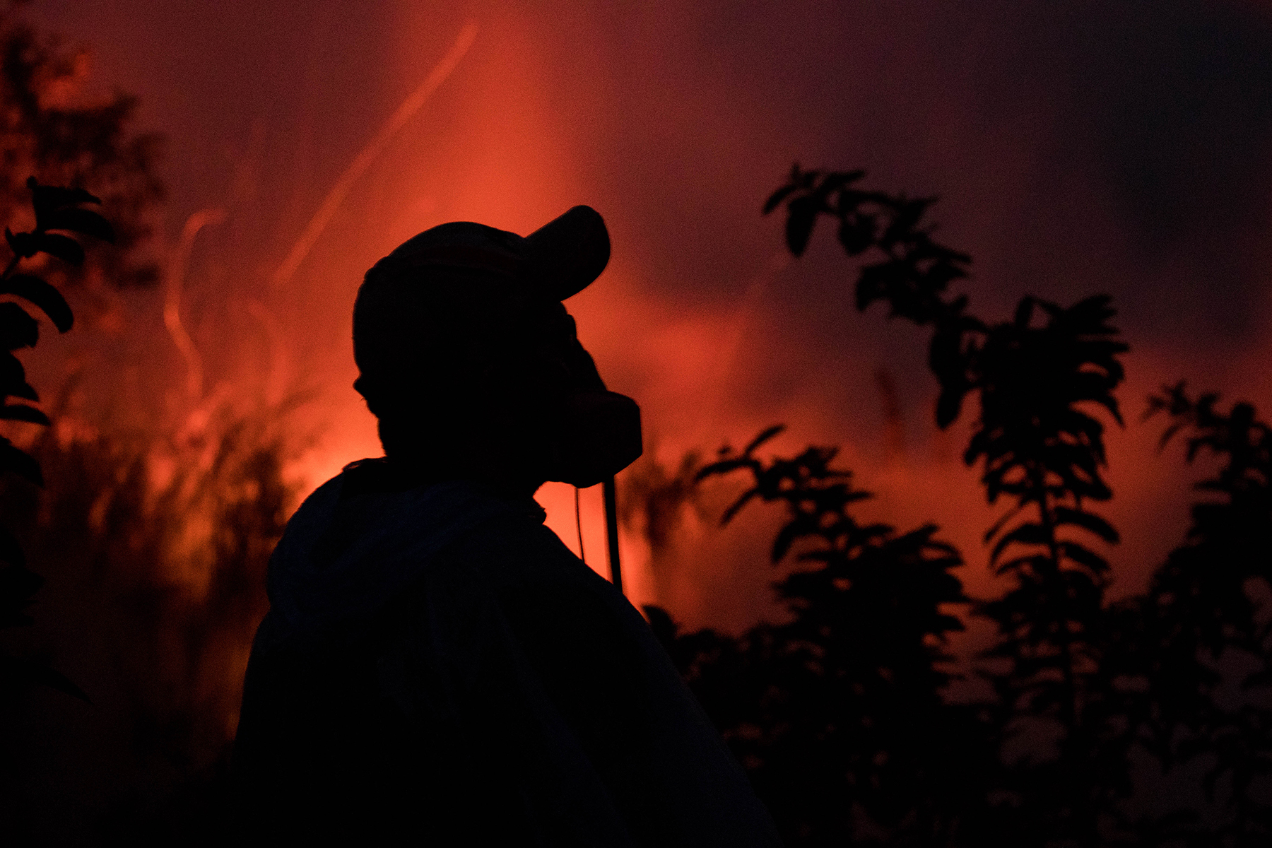 <p>Journalist Joseph Anthony stands in the glow of the beginnings of a new volcanic fissure on Saturday evening. He is wearing a respirator for protection against sulfur dioxide gases.</p>