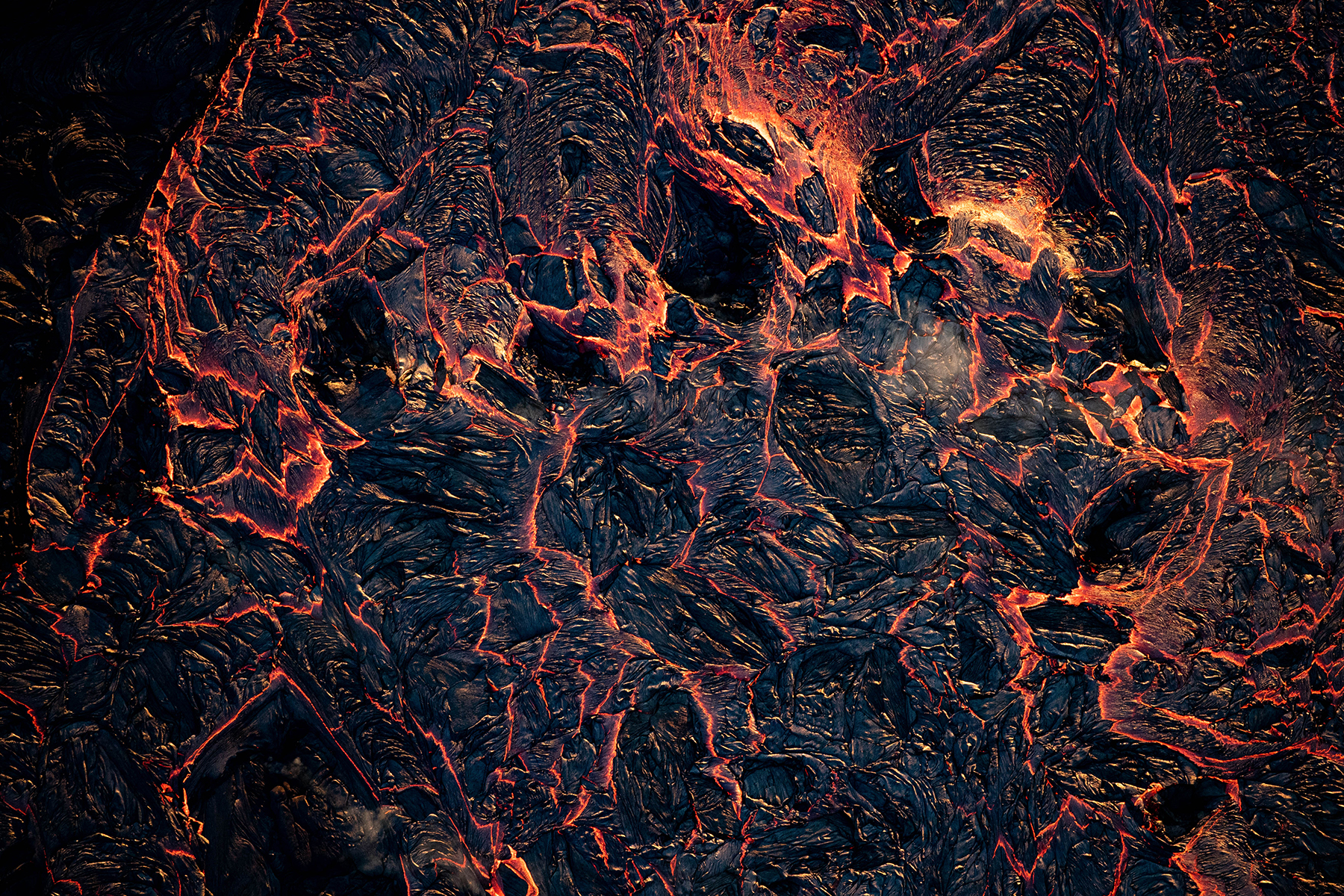 <p>As lava flows away from the fissure, the surface begins to cool and solidify, cracking as it continues to move.</p>