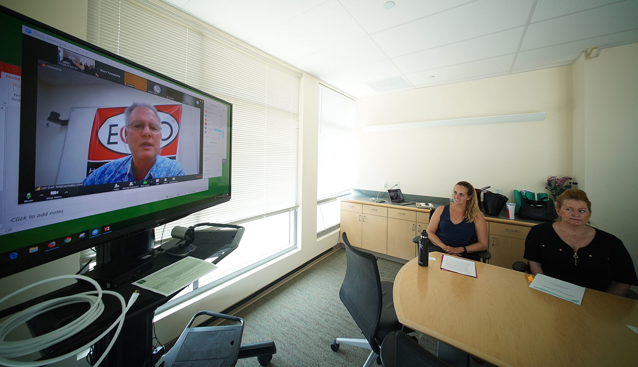Left, Lindsey Kaumeheiwa, Dept of Health Expert Project Coordinator and right, Hawaii Substance Abuse Coalition, Expert Referral Coordinator Bebe Bainum speak to a group of folks on the screen at left at UH Medical School located in Kakaako.