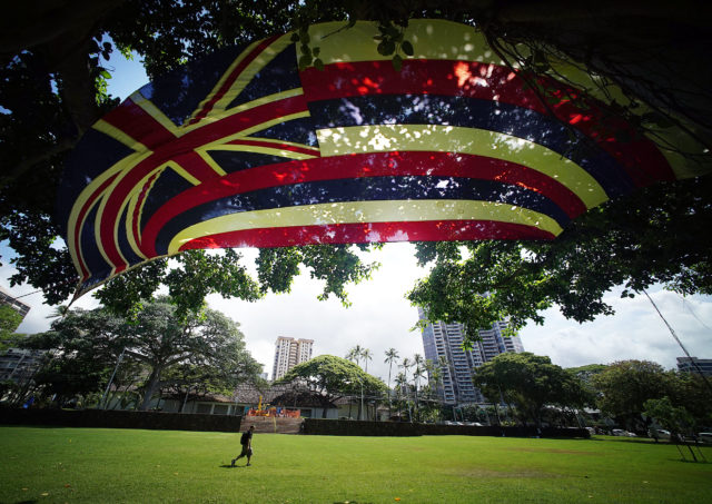 Large Hawaiian Flag flies on mauka side of Thomas Square near Kamehameha III dedication ceremonies held on July 31, also celebrated as Lā Hoʻihoʻi Ea, Sovereignty Restoration Day, an official national holiday of the kingdom of Hawaii.