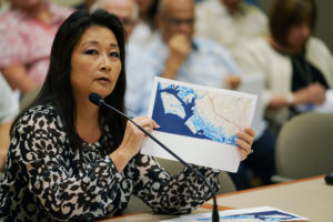 Rep Sylvia Luke holds graphic ocean inundation areas in Kakaako HART Meeting in Kapolei.