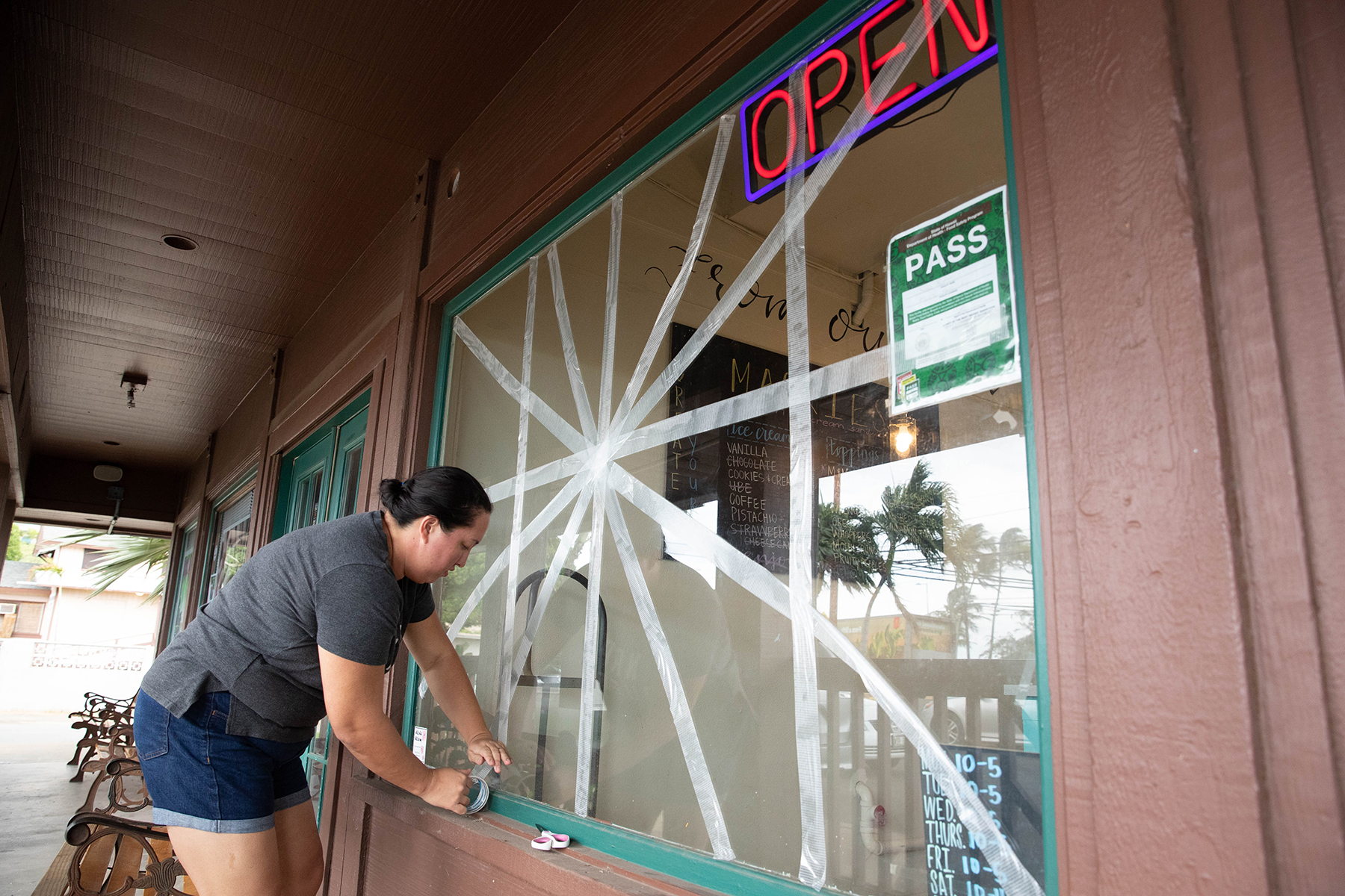 <p>There are different theories about how to prevent windows from breaking in a windstorm. Shivon Lave chose the tape option for her bakery in Maili. Photograph by Anthony Quintano/Civil Beat</p>