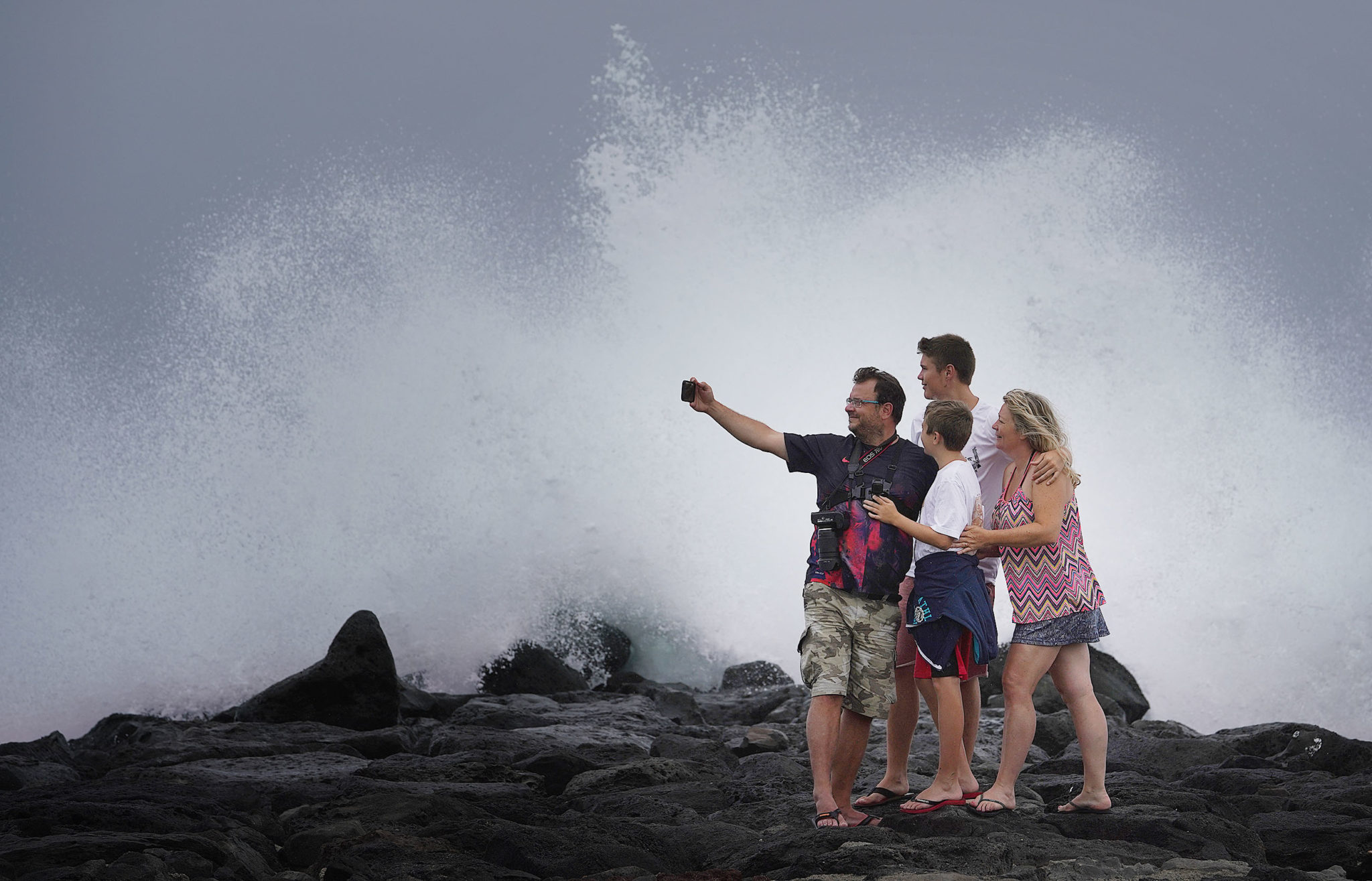 <p>For some, the churning surf in advance of the storm was just one more tourist attraction. That included the Demoersman family visiting from France and taking a selfie with a crashing wave at Magic Island. Photograph by Cory Lum/Civil Beat</p>