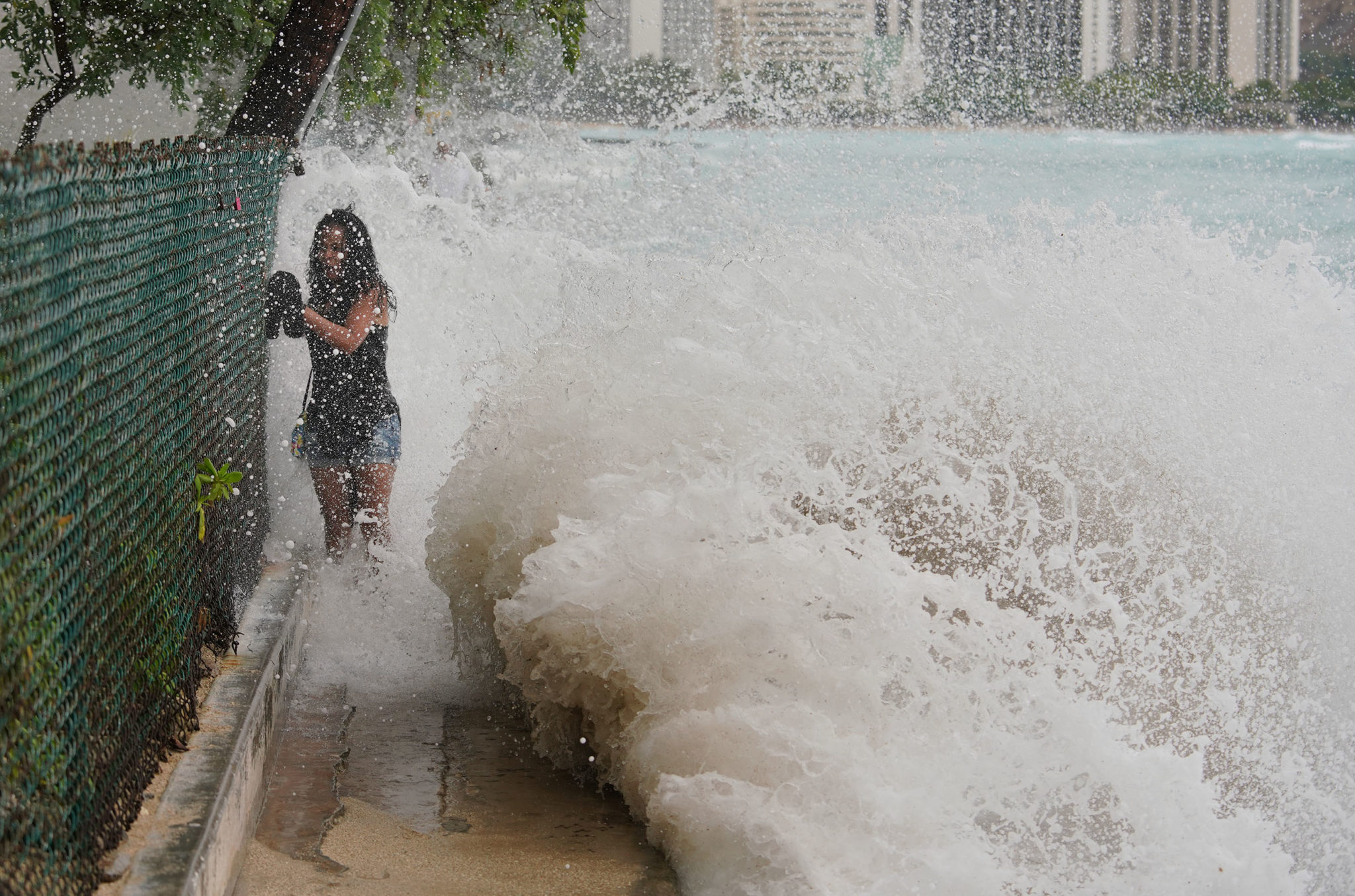 <p><strong>THE THREAT PASSES:</strong> High-altitude winds subdued the hurricane and pushed it away from Hawaii, although there was flooding on the Big Island, storm-related wildfires on Maui and big surf everywhere else, including near a woman walking next to the Outrigger Hotel in Honolulu. / Cory Lum</p>