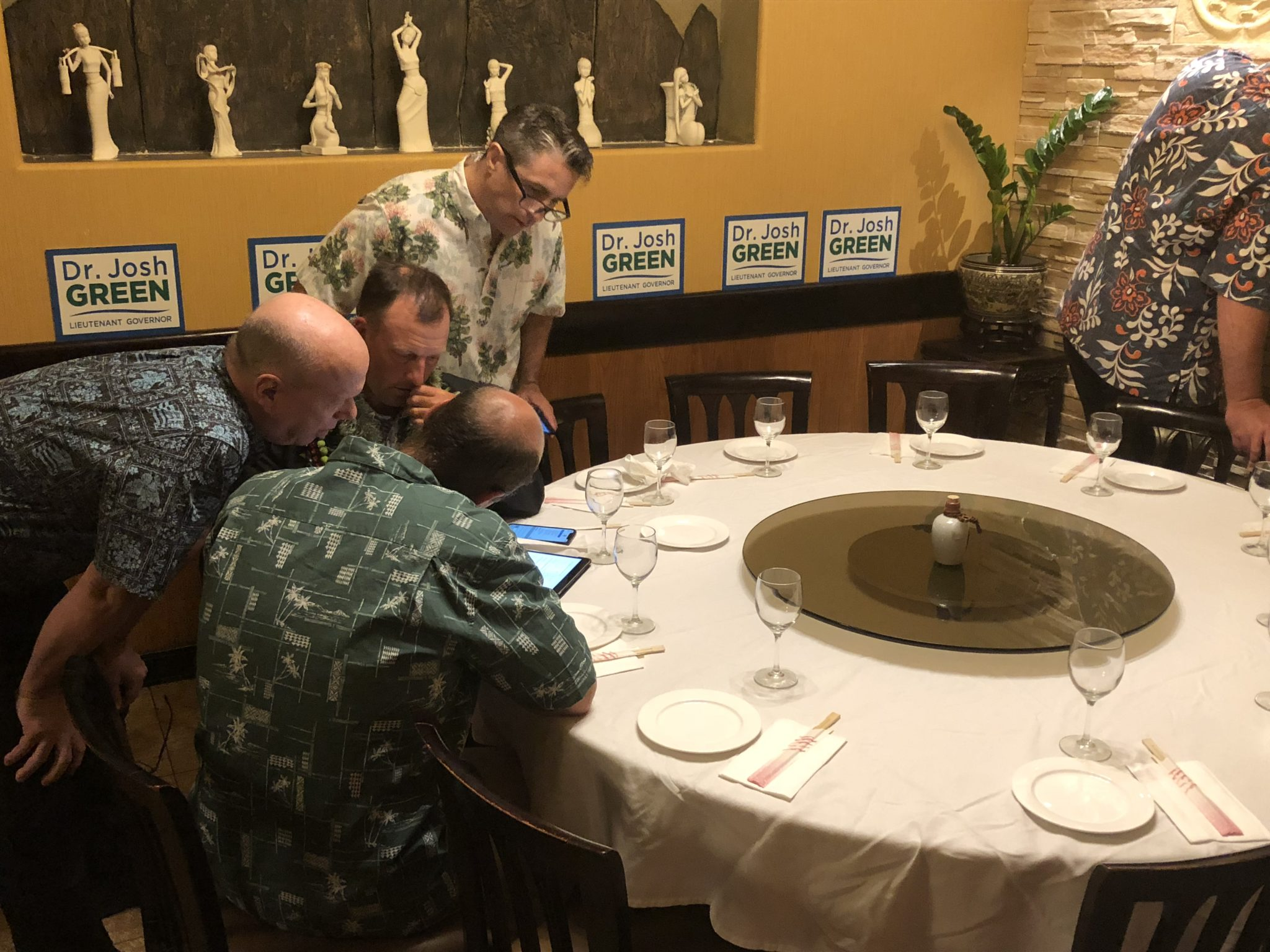 <p>State Sen. Josh Green, right center, checks early returns at the Little Village Noodle House that show him leading in the Democratic primary for lieutenant governor.</p>