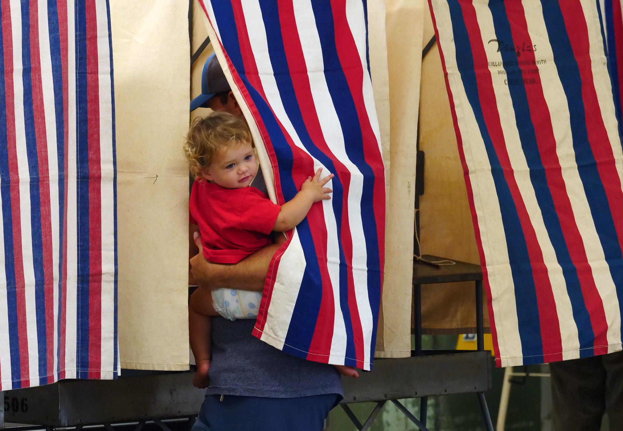 <p>Taj Brady, 1, peeks from behind the voting booth curtain as his father, Sean Brady, votes at Kailua Elementary School on Saturday morning.</p>