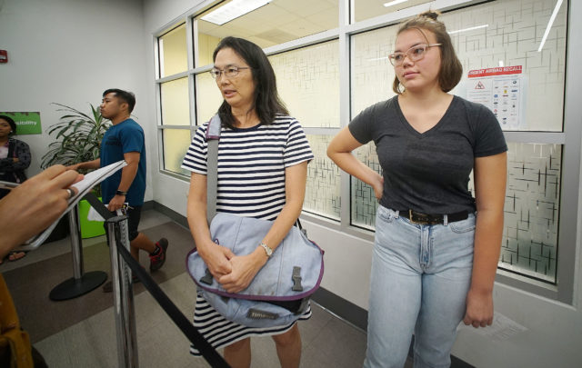 Andrea Bender with her daughter, right, 16-year-old Emily Bender stand in line at the Kapalama Driver License Office of Honolulu.