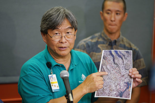 Board of Water Supply Ernest Lau holds evacuation diagram if dam is compromised or is damaged from too much water.