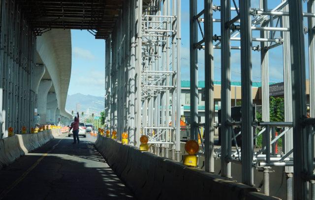 Worker stops the single lane going west on Kamehameha Hwy near the future Pearlridge rail station.