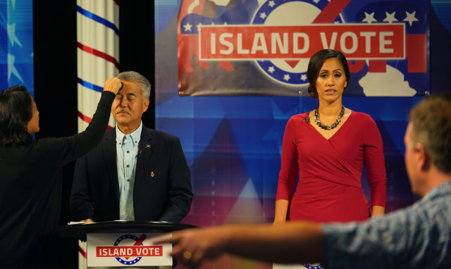 Makeup artist works on Gov David Ige before the iive gubernatorial debate with challenger Andria Tupuola at right.