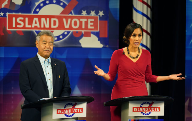 Andria Tupuola gestures as Gov David Ige looks on during gubernatorial debate.