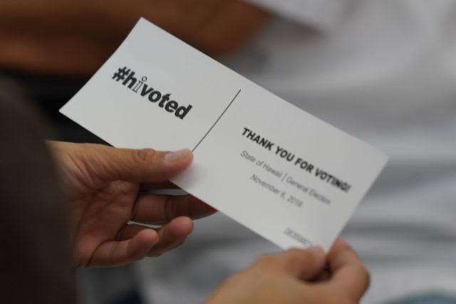 Voter holds their paper ballot stub at Farrington High School.