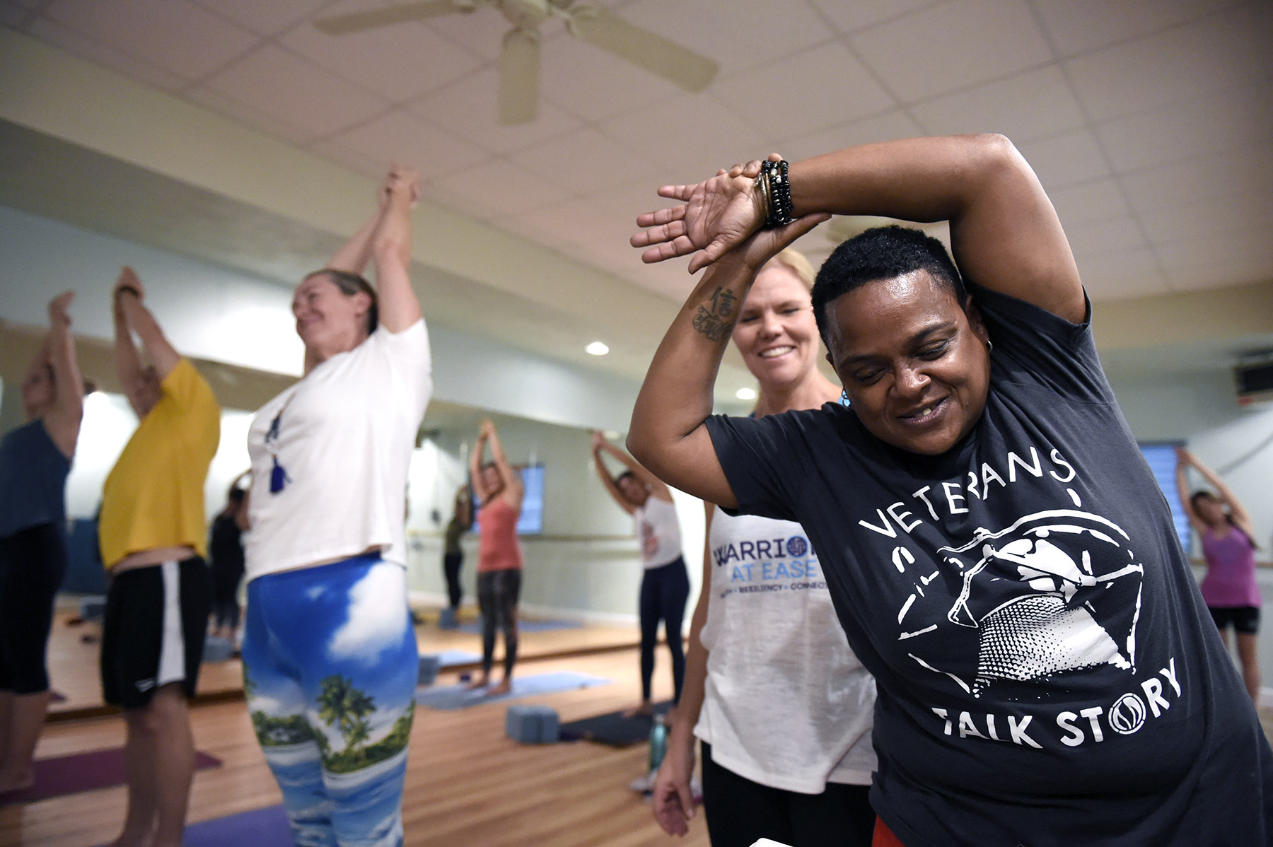 Cyndi Lee smiles while stretching as Susan Alden looks on during a yoga class created to help US military Veterans cope with PTSD called Warriors At Ease at the Bella Kai Yoga Studio in Kailua, Wednesday, November 7, 2018. (Civil Beat photo Ronen Zilberman)
