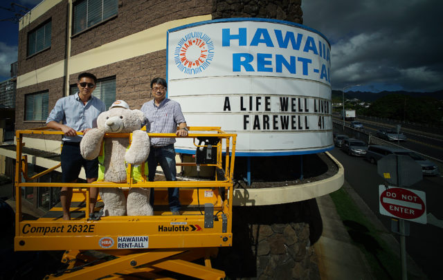 Nathan Oh with right, Scott Jung in portrait with Hawaiian Rent All's mascot center, Rentie fronting their sign board located at McCully Street and South Beretania Street.