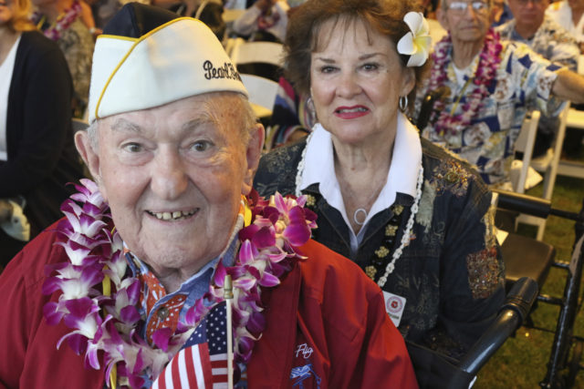 John Mathrursse, a 95-year-old Pearl Harbor survivor from Mountain View, Calf., left, and his wife Miriam Hoppe Malthrusse pose for a photo before a ceremony in Pearl Harbor, Hawaii on Friday, Dec. 7, 2018 marking the 77th anniversary of the Japanese attack. The Navy and National Park Service jointly hosted the remembrance ceremony at a grassy site overlooking the water and the USS Arizona Memorial. (AP Photo/Audrey McAvoy)