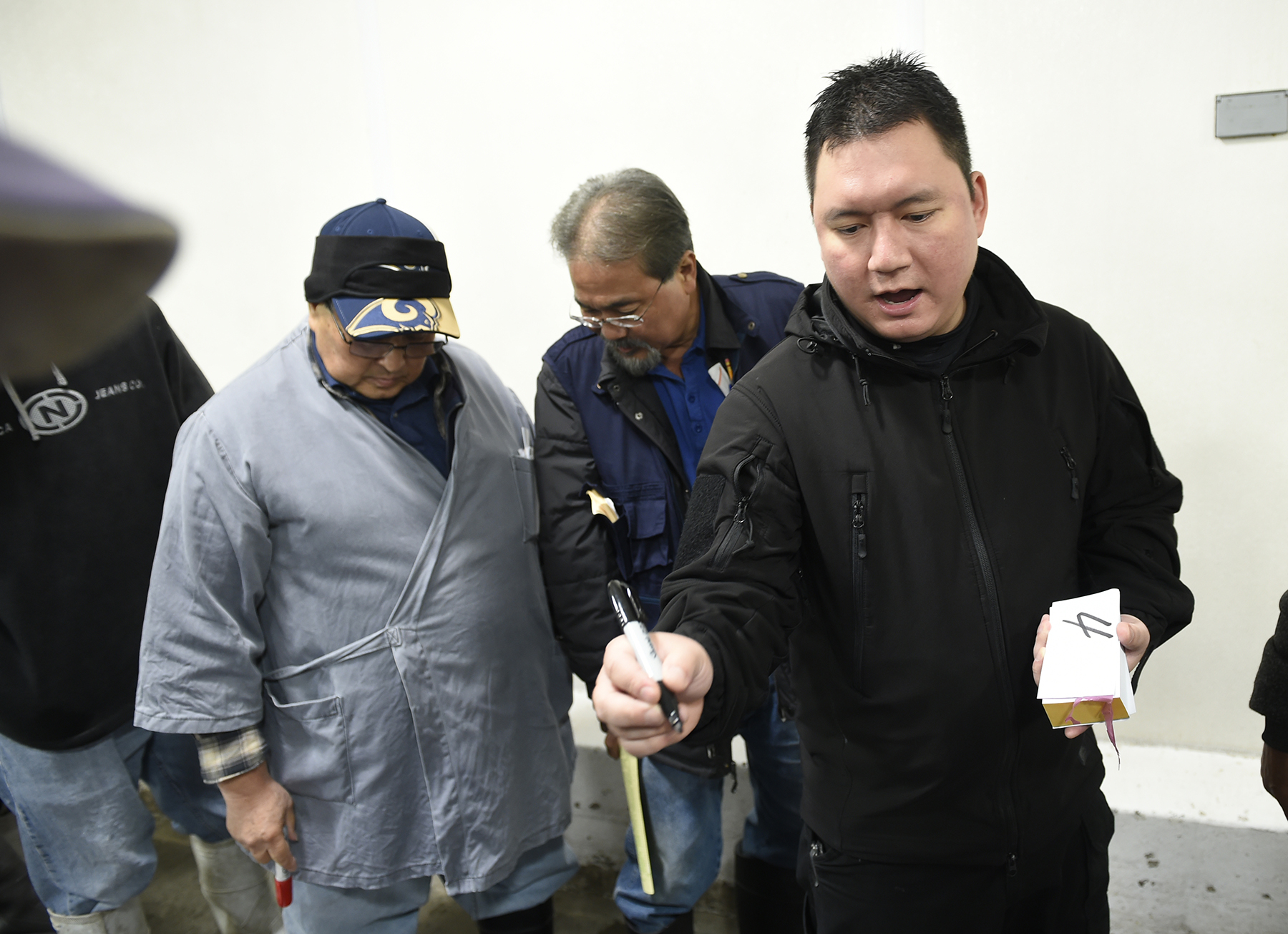 <p>Auctioneer Michael Goto, right, calls the bids. Higher-quality ahi command the highest prices and the competitive open bidding process continues until every fish is sold.</p>