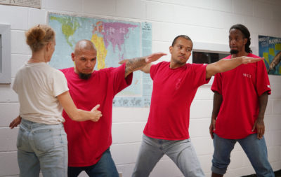 Yoga Teacher Lu DiGrazia teaches a class in the Waiawa Prison, Hale Malamama with left to right, William Brooks, Dante Rackley and right, Brendan Hill.