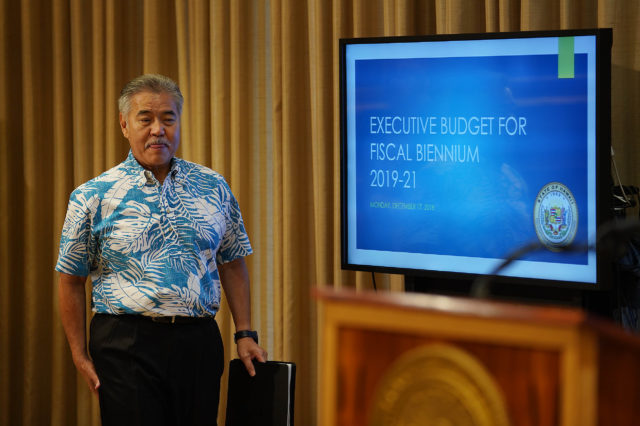 Governor David Ige walks into press conference past computer screen at the Capitol.