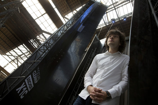 FILE - In this May 11, 2017, file photo, Dutch innovator Boyan Slat poses for a portrait next to the anchors of his plastic collecting system, suspended from the roof of a building in Utrecht, Netherlands. The trash collection device deployed to corral plastic litter floating between California and Hawaii in an attempt to clean up the world's largest garbage patch is not collecting any trash. Slat, who launched the Pacific Ocean cleanup project, told The Associated Press in an interview Monday, Dec. 17, 2018, he is confident the 2,000-foot (600-meter) long floating boom will be fixed.(AP Photo/Peter Dejong, File)