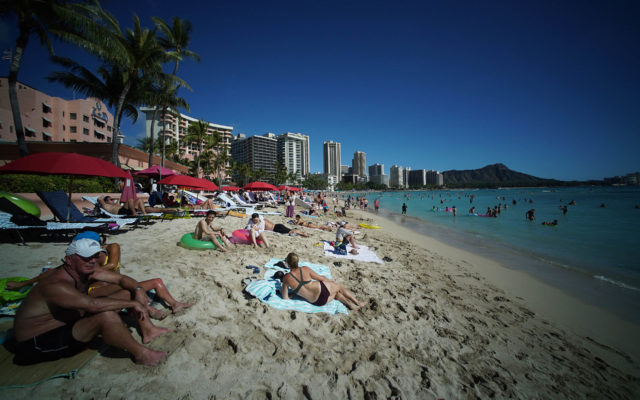 Visitors to Oahu's Waikiki Beach with Diamond Head in the background.