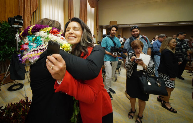 Congresswoman Tulsi Gabbard greets new council member Heidi Tsuneyoshi during recess.