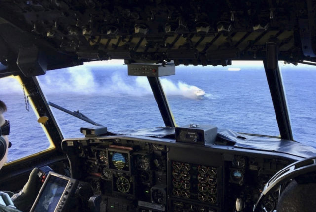 In this Dec. 31, 2018 photo provided by the U.S. Coast Guard, a Coast Guard HC-130 Hercules aircrew flies over the 650-foot Sincerity Ace on fire 1,800 nautical miles northwest of Oahu in the Pacific Ocean. The U.S. Coast Guard is suspending its search for a crew member from a vessel carrying cars from Japan to Hawaii who went missing after the ship caught fire. The Coast Guard made the decision to suspend the search for the Sincerity Ace crew member on Wednesday, Jan. 2, 2019. (U.S. Coast Guard via AP)