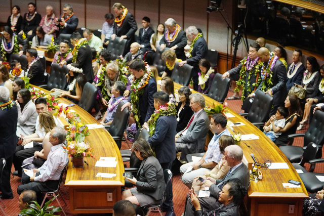 House Members bedecked in lei on the house floor at the Capitol on opening day.
