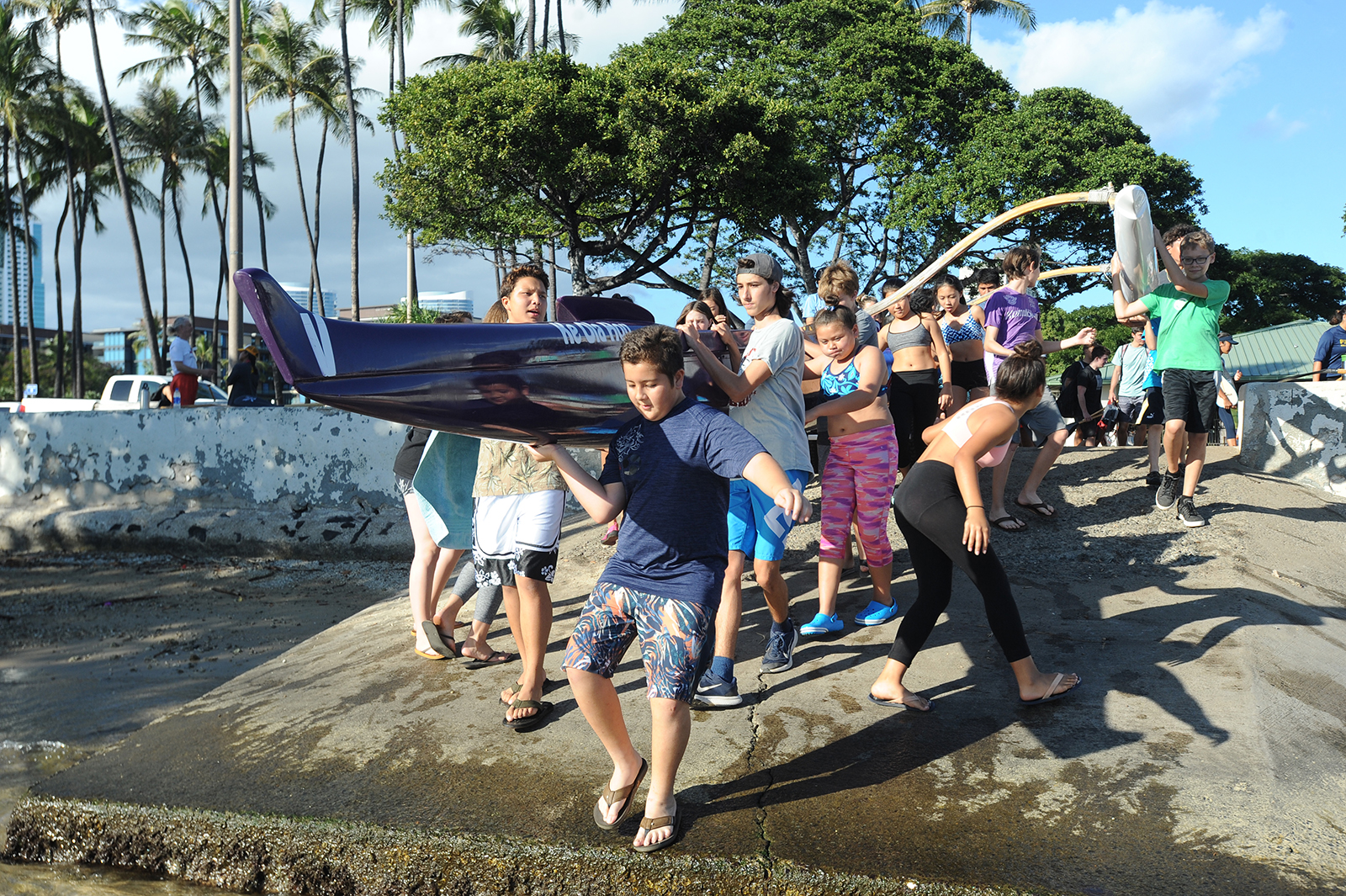 <p>Members of the Elks Kumulokahi Canoe Club's youth paddling team haul their outrigger canoe into the water for a January practice at Magic Island.</p>