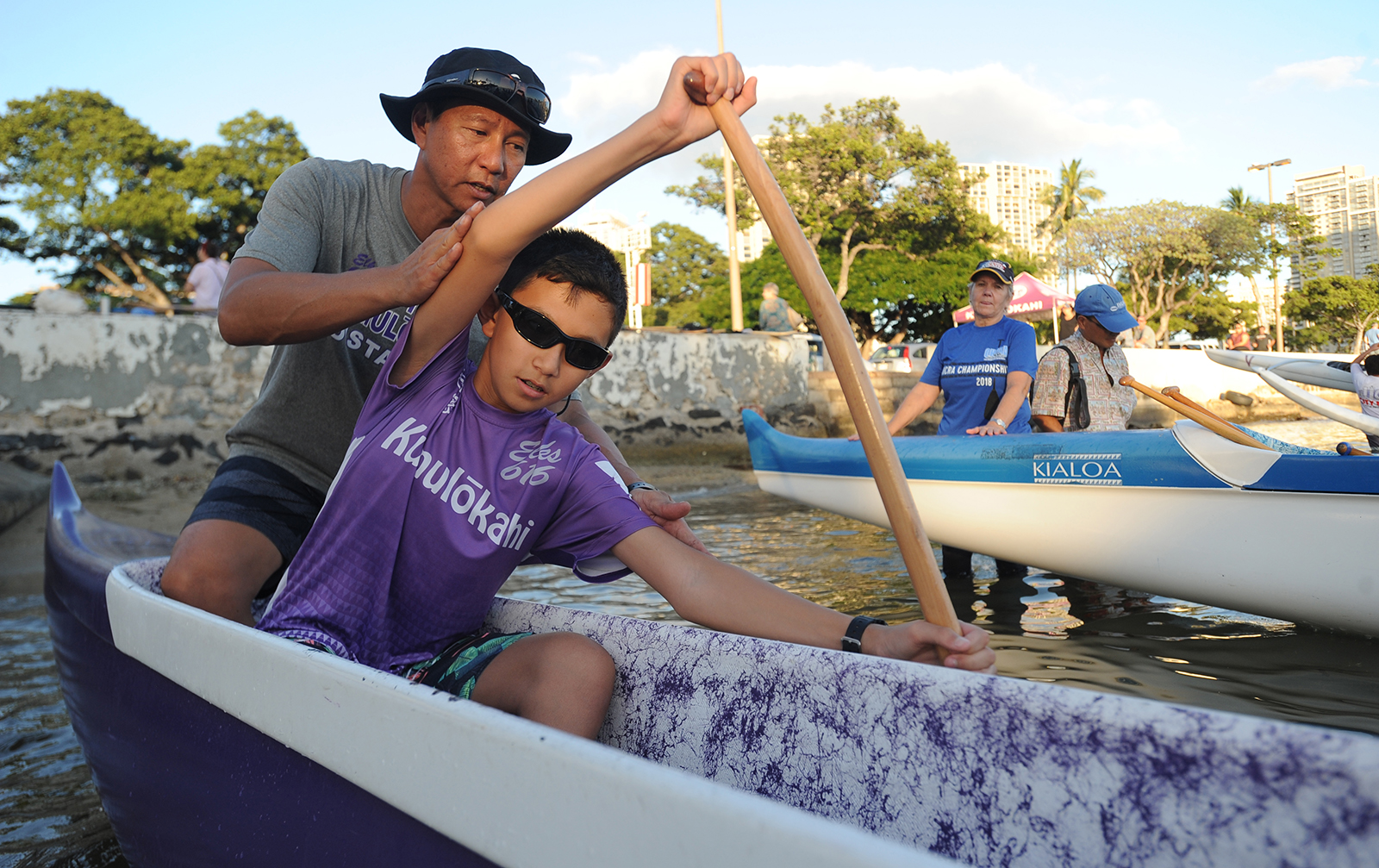 <p>Youth paddling coach Kevin Kam instructs his son, Shafer, in stroking technique during a practice session.</p>