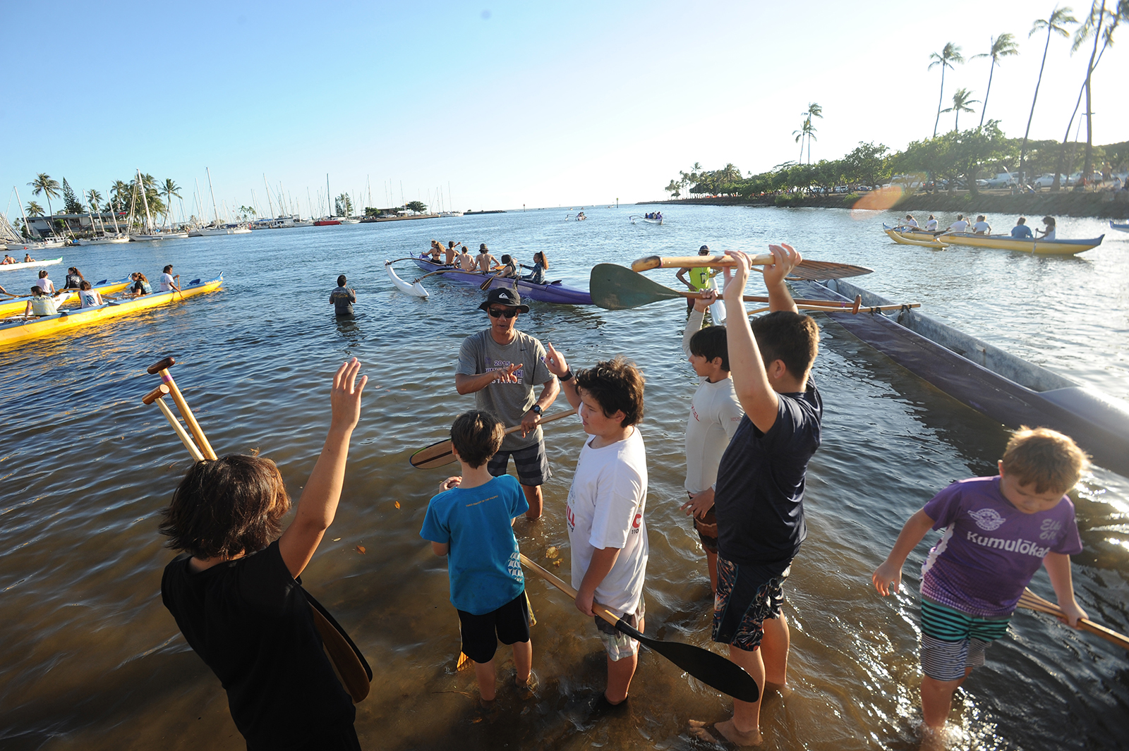 <p>Youth paddling team members raise their hands to get a turn in a canoe. The club ensures that everyone who wants to paddle and is willing to work hard gets a chance.</p>