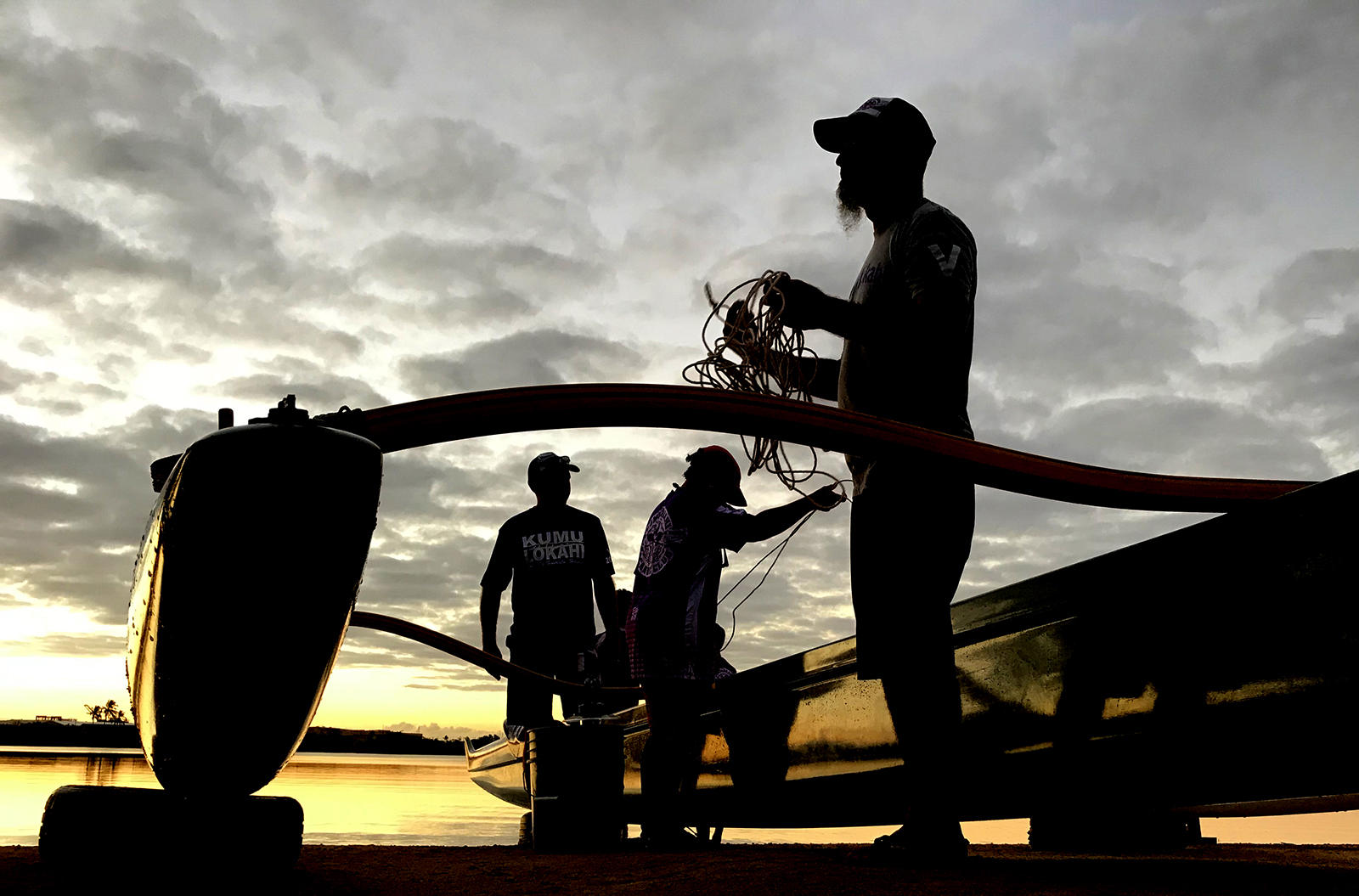 "<p>The Jan. 12 Hui Wa'a race day at Keehi Lagoon Beach Park starts before sunrise as coaches and volunteers, from left, Jim Bauckham, Tambry Young and Sean Gallagher, tie the ""ama"" (outrigger) to a canoe.</p>"
