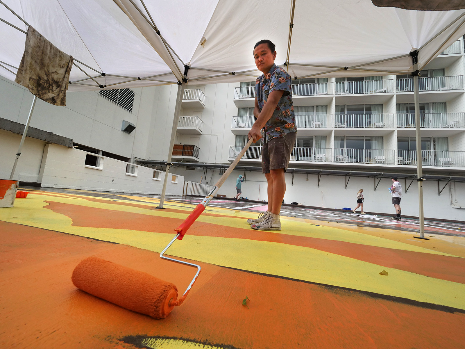 <p>Artist Victor Ving rolls paint onto the surface of his mural at the Alohilani Resort in Waikiki on Jan. 29, the first day of the latest installment in his quest to create landmarks through public art in each of the 50 states.</p>