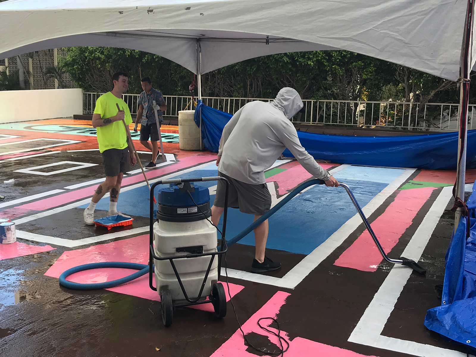<p>The Greetings Tour crew clears water off the surface of the mural. Near-constant rain forced them to use tarps and a water vacuum throughout the week.</p>
