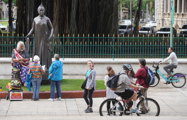 Cyclists ride past pedestrians near the Queen Liliuokalani Statue.