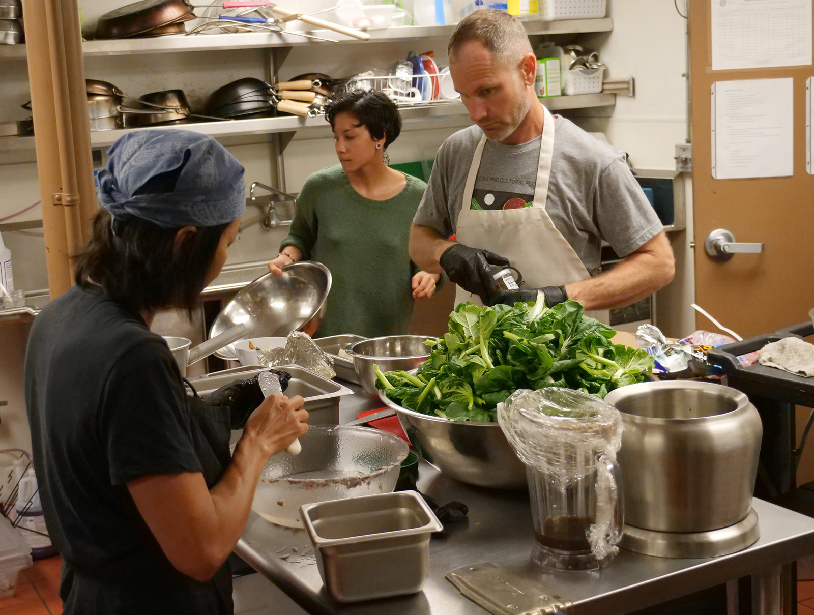 <p>Roots Cafe head chef Jesse Lipman, right, and volunteers prepare lunch Feb. 7 with produce grown farther up the valley at Ho'oulu Aina. The cafe inside the Kalihi Health Center is open to the public Tuesdays and Thursdays from 11:30 a.m. to 1:30 p.m.</p>