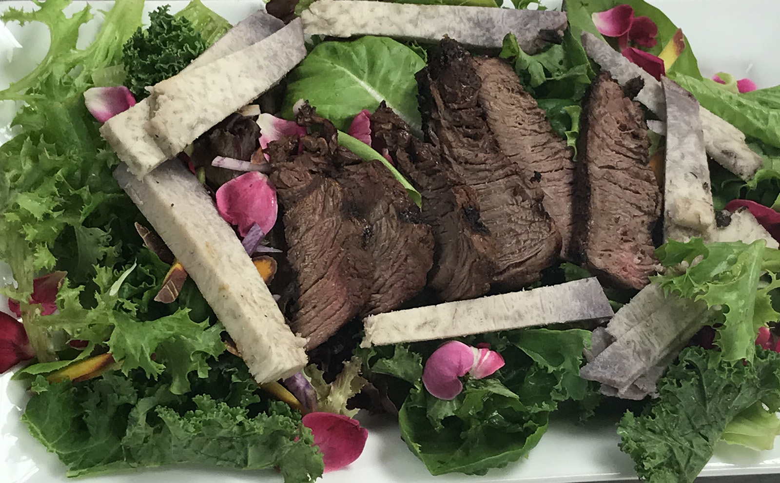 <p>The Roots Cafe focuses on healthy entrees featuring mostly local ingredients such as this organic salad with steak and kalo pa'a. The cafe is also used for culinary training, discussion groups, speaker engagements, film nights and cultural celebrations.</p>