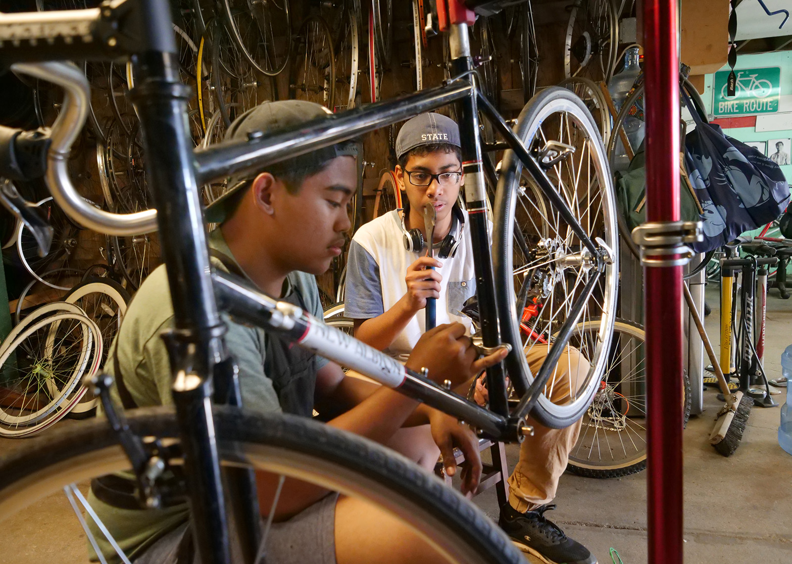 "<p>Lesson Guarin, left, and Aliipo Edgar work on a bicycle Feb. 20 that now belongs to Aliipo thanks to his hours of volunteering at the bike shop. The program gives kids a safe place to socialize and learn skills, but is also open to participants ""as young as 77 years,"" says KVIBE director Kevin Faller.</p>"