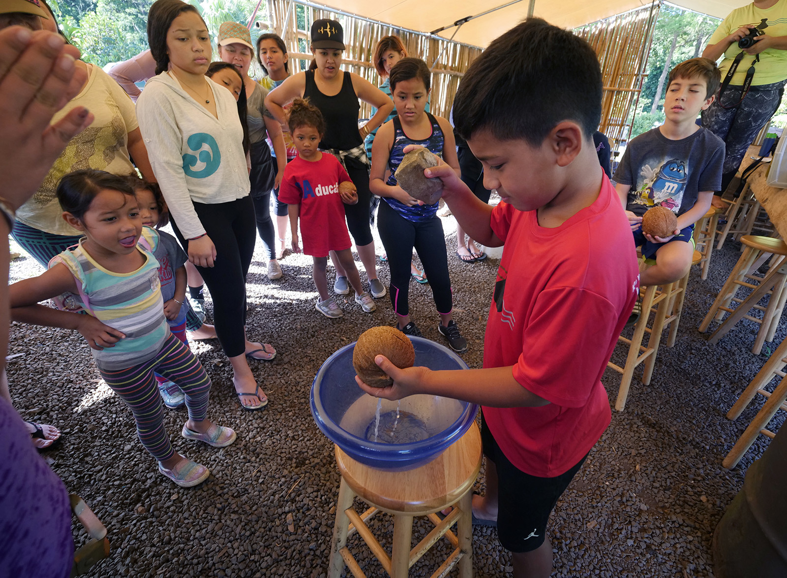 "<p>Eonsa Lyman, 10, cracks open a coconut for the first time during the community lesson. On its website, Kokua Kalihi Valley says it serves over 10,000 people a year ""to foster health in the broadest sense — physical, mental, emotional and spiritual.""</p>"