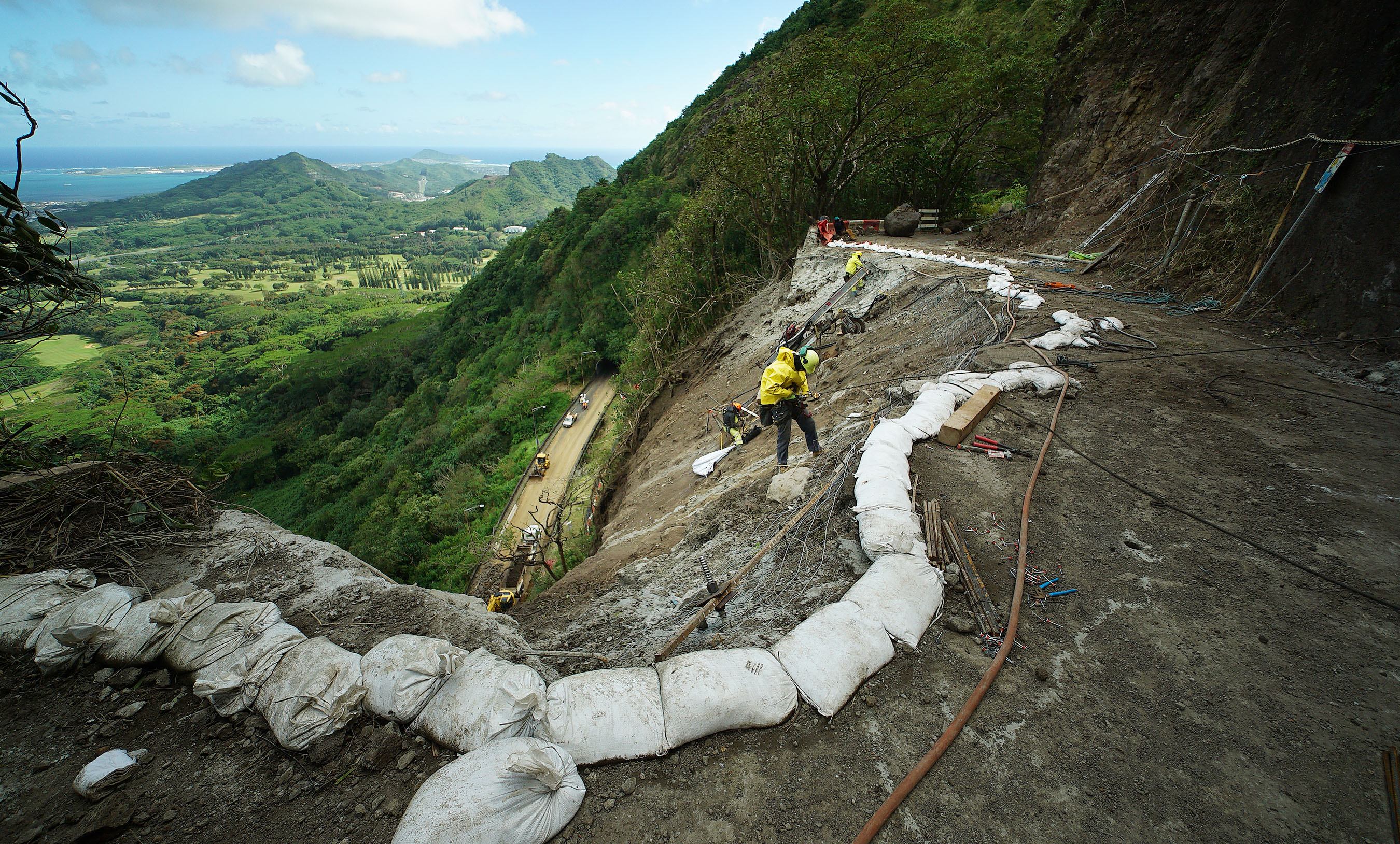 <p>Workers rappel down the damaged slope alongside Old Pali Road with a view of the highway below.</p>