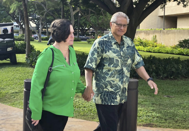 In this photo taken Tuesday, March 12, 2019, retired Honolulu police chief Louis Kealoha and his wife, former deputy city prosecutor Katherine Kealoha, hold hands while walking to U.S. district court in Honolulu. A judge has approved a $1.3-million cash sale for the former home of the Kealohas, who are mired in a federal corruption investigation. (AP Photo/Jennifer Sinco Kelleher)