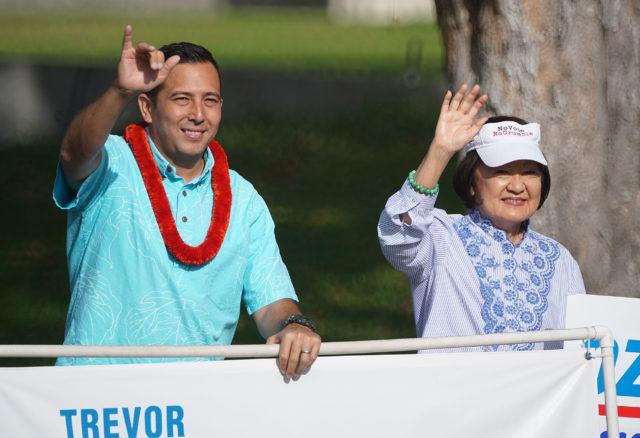 City Council candidate Trevor Ozawa waves with right Ann Kobayashi at Beretania Punchbowl street.