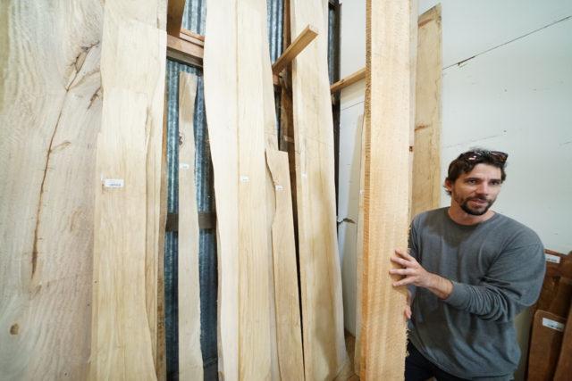 Waimanalo Wood Miles Luedtke stands holding Albezia plank.