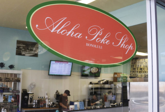 """This Tuesday, April 16, 2019, photo shows Aloha Poke Shop, a store in Honolulu that received a letter from Chicago-based Aloha Poke Co. saying the Illinois company had trademarked """"Aloha Poke"""" and the Hawaii company would need to change its name. Hawaii lawmakers are considering adopting a resolution calling for the creation of legal protections for Native Hawaiian cultural intellectual property. (AP Photo/Audrey McAvoy)"""