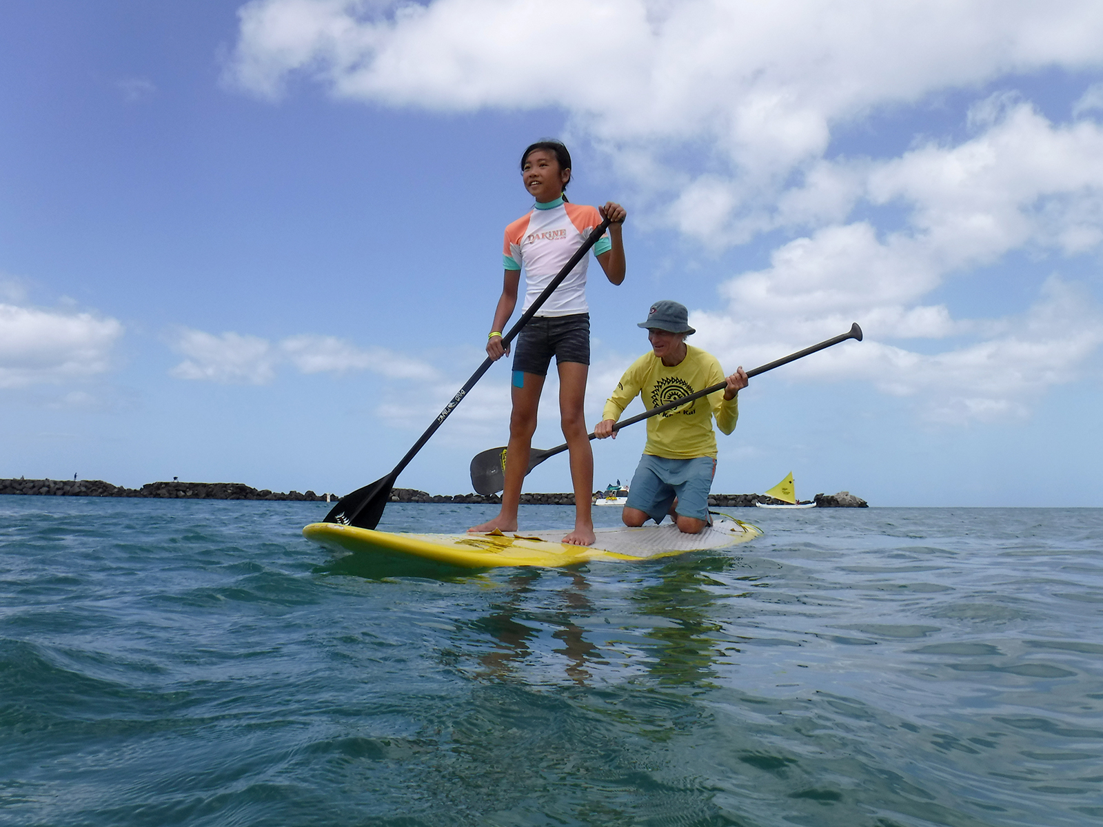 <p>Joyce Wong of Honolulu, left, and volunteer Jack Sutherland enjoy a paddle board ride. Kids are treated to group and one-on-one interactions with ocean professionals such as lifeguards, firefighters, marine scientists, Hawaiian cultural practitioners and ocean rescue instructors.</p>